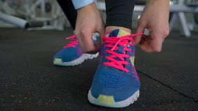 Running shoes - woman tying shoe laces in the gym. Running shoes - woman tying shoe laces. Closeup of fitness woman getting ready for engage in the gym stock video footage