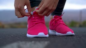 Running shoes - woman tying shoe laces on a desert road in a mountainous area. Slow motion. Running shoes - woman tying shoe laces on a desert road in a stock footage