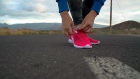 Running shoes - woman tying shoe laces on a desert road in a mountainous area. Slow motion. Running shoes - woman tying shoe laces on a desert road in a stock video footage