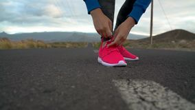Running shoes - woman tying shoe laces on a desert road in a mountainous area. Slow motion. Running shoes - woman tying shoe laces on a desert road in a stock video
