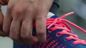 Running shoes - woman tying shoe laces in the gym stock footage