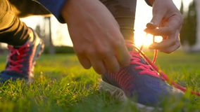 Running shoes - woman tying shoe laces. Slow motion. Running shoes - woman tying shoe laces. Closeup of woman ties up her shoelaces on sneakers while running in stock footage