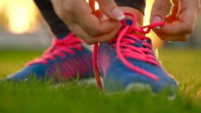 Running shoes - woman tying shoe laces. Slow motion. Running shoes - woman tying shoe laces. Closeup of woman ties up her shoelaces on sneakers while running in stock video