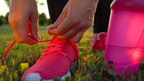 Running shoes - woman tying shoe laces. Slow motion. Running shoes - woman tying shoe laces. Closeup of woman ties up her shoelaces on sneakers while running in stock video footage