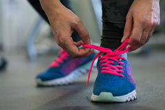 Running shoes - woman tying shoe laces. Woman getting ready for. Running shoes - woman tying shoe laces. Closeup of fitness woman getting ready for engage in the stock image