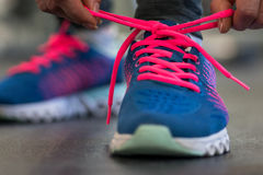 Running shoes - woman tying shoe laces. Woman getting ready for. Running shoes - woman tying shoe laces. Closeup of fitness woman getting ready for engage in the royalty free stock images
