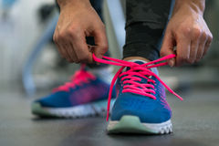 Running shoes - woman tying shoe laces. Woman getting ready for. Running shoes - woman tying shoe laces. Closeup of fitness woman getting ready for engage in the royalty free stock image