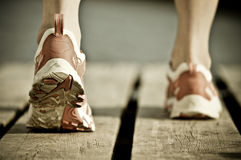 Running shoes on wood. Feet of a person wearing running shoes on wooden planks royalty free stock photography