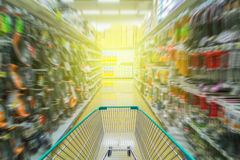Running shopping cart in supermarket Royalty Free Stock Photography