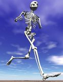 Running skeleton. 3D jogging skeleton with blue sky and sand Royalty Free Stock Images