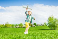 Running small boy holding airplane toy in  meadow Stock Photo
