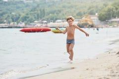 Running Smiling boy on the beach stock photo
