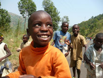 Running Smiling Burundian Kids. A group of smiling children run along a road outside of Bujumbura, Burundi Stock Photos