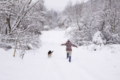 Running in the snow. Girl and a dog running together through the snow Stock Photos
