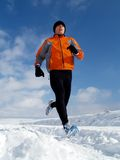 Running in Snow. An athlete exercising on a cold winter day Royalty Free Stock Photos