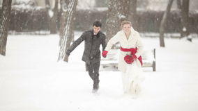 Running in the snow bride and groom. The bride and groom running on snow. The camera on the steadicam stock video