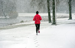 Running in snow. A woman running in the snow in the winter Stock Photos