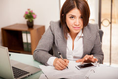 Running some numbers at work. Cute accountant using her smart phone to do some calculations at work Royalty Free Stock Photography