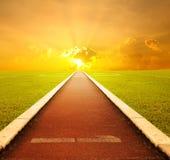 Running spår med en lane med solnedgången för succes Arkivfoto