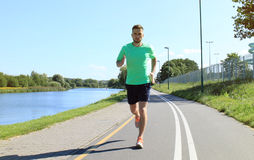 Running sport man. Fit muscular young male runner sprinting at great speed outdoors on road Royalty Free Stock Images