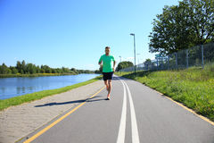 Running sport man. Fit muscular young male runner sprinting at great speed outdoors on road Stock Photo