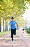 Running sport man. Fit muscular young male runner sprinting at great speed outdoors on road. Handsome male fitness sport model outdoors Stock Photos
