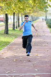 Running sport man. Fit muscular young male runner sprinting at great speed outdoors on road. Handsome male fitness sport model outdoors Royalty Free Stock Photography