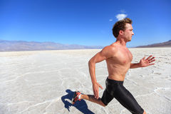Running sport man - fitness runner in desert. Running sport man - fitness runner sprinting in desert shirtless. Fit sports model athlete man during sprint run at royalty free stock photography