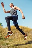 Running sport. Man runner sprinting outdoor in scenic nature. Fit muscular male athlete training trail running for Stock Photo