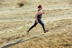 Running sport. Man runner sprinting outdoor in scenic nature. Fit muscular male athlete training trail running for Royalty Free Stock Photos