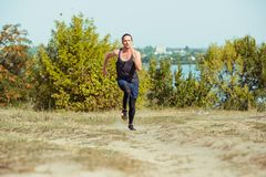 Running sport. Man runner sprinting outdoor in scenic nature. Fit muscular male athlete training trail running for Stock Photos