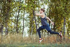 Running sport. Man runner sprinting outdoor in scenic nature. Fit muscular male athlete training trail running for Stock Image