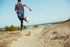 Running sport. Man runner sprinting outdoor in scenic nature. Fit muscular male athlete training trail running for. Marathon run. Sporty fit athletic man Royalty Free Stock Photography