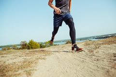 Running sport. Man runner sprinting outdoor in scenic nature. Fit muscular male athlete training trail running for Stock Images