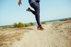 Running sport. Man runner sprinting outdoor in scenic nature. Fit muscular male athlete training trail running for. Marathon run. Sporty fit athletic man Stock Photography