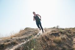 Running sport. Man runner sprinting outdoor in scenic nature. Fit muscular male athlete training trail running for. Marathon run. Sporty fit athletic man Royalty Free Stock Photos