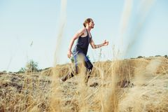 Running sport. Man runner sprinting outdoor in scenic nature. Fit muscular male athlete training trail running for. Marathon run. Sporty fit athletic man Stock Images