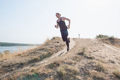 Running sport. Man runner sprinting outdoor in scenic nature. Fit muscular male athlete training trail running for. Marathon run. Sporty fit athletic man Royalty Free Stock Images