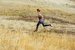 Running sport. Man runner sprinting outdoor in scenic nature. Fit muscular male athlete training trail running for Royalty Free Stock Images