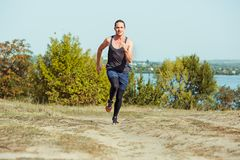 Running sport. Man runner sprinting outdoor in scenic nature. Fit muscular male athlete training trail running for Stock Photography