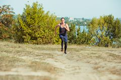 Running sport. Man runner sprinting outdoor in scenic nature. Fit muscular male athlete training trail running for. Marathon run. Sporty fit athletic man Stock Image