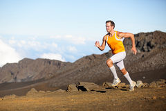 Running sport runner man sprinting in trail run. Fit male fitness sports athlete training sprint in amazing outdoor trail on volcano. Strength and success Stock Photo