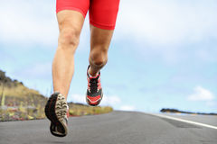 Running sport runner shoes and legs. Running sport shoes and legs. Man runner legs and shoes in action on road outdoors at sunset. Male athlete model stock photography