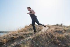 running sport Sprinta för manlöpare som är utomhus- i scenisk natur Färdig muskulös manlig spring för idrottsman nenutbildningssl royaltyfria bilder