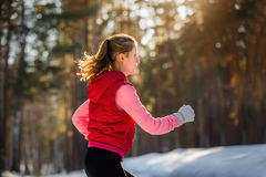 Running sport woman. Female runner jogging in cold winter forest Stock Photography