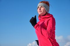 Running sport woman. Female runner jogging in cold winter forest wearing warm sporty running clothing and gloves.  royalty free stock images