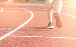 Running sport. Woman runner legs and shoes in action on track outdoors at sunset. stock photography