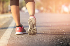 Running sport. Woman runner legs and shoes in action on track outdoors at sunset. royalty free stock photos