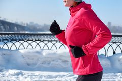 Running sportkvinna Kvinnlig löpare som joggar i den kalla vinterstaden som bär varma sportiga rinnande kläder och handskar royaltyfri fotografi