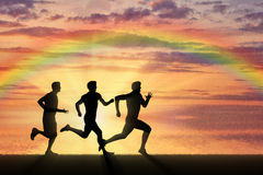 Running sports. Competition athletes three runners Stock Photo